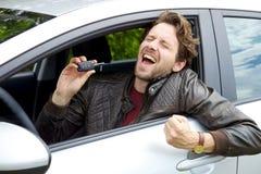 Erfolgreicher glücklicher Mann, der Schlüssel des Neuwagens hält stockfoto