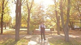 Erfolgreicher hübscher Geschäftsmann setzt an eine Jacke in den Herbst Park ein stock video