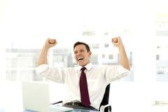 Erfolgreicher junger Geschäftsmann am Arbeitsplatz Stockfotografie