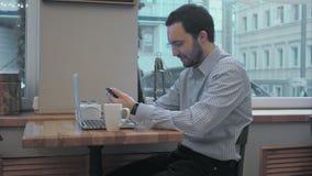 Erfolgreicher junger Geschäftsmann unter Verwendung des Zelltelefons während der Kaffeepause im Café nach innen stock footage