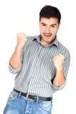 Erfolgreicher junger Mann, der Kamera betrachtend feiert Lizenzfreie Stockfotografie