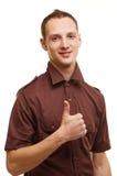 Erfolgreicher junger Mann, der sich Daumen zeigt Lizenzfreie Stockbilder