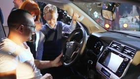 Erfolgreicher Kauf, Familie wählt neues Fahrzeug und betrachtet mit Interessensalon stock video footage