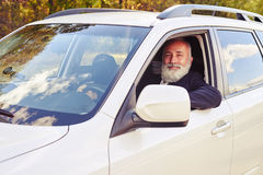 Erfolgreicher älterer Geschäftsmann, der vom Fenster schaut Lizenzfreies Stockfoto