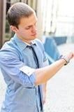 Erfolgreicher Mann, der seine Uhr betrachtet. Stockfoto
