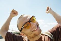 Erfolgreicher Mann in der Sonnenbrille mit den Armen oben Stockfotografie