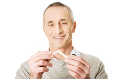 Erfolgreicher Mann mit defekter Zigarette Stockfoto