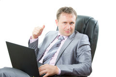 Erfolgreicher Mann mit dem Laptop, der sich Daumen zeigt Stockfotografie
