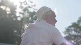 Erfolgreicher positiver lächelnder reifer Mann, der Tennis auf dem Tennisplatz spielt Der alte Mann wirft den Ball mit dem Schläg stock footage