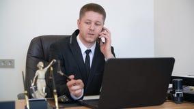 Erfolgreicher Rechtsanwalt, der einen Telefonanruf in seinem Büro nimmt Sprechen Sie Telefon mit Kunden und das Versuchen, die Sa stock footage