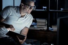 Erfolgreicher reifer Kerl, der später an Laptop nachts arbeitet Stockbild