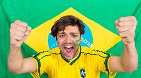 Erfolgreicher Sportler, der gegen brasilianische Flagge schreit Stockfotografie