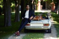 Erfolgreicher und wohlhabender Geschäftsmann, der einen Tag während der Reise auf Luxuscabrioletauto auf Landschaftsstraße genieß lizenzfreies stockbild