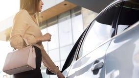 Erfolgreicher weiblicher Grundstücksmakler, der in Fahrzeug nach Arbeitstag in der Agentur kommt lizenzfreies stockfoto