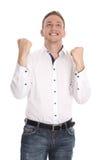 Erfolgreicher zujubelnder lokalisierter junger blonder Mann, der Faustgeste macht Stockfoto