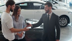 Erfolgreiches Abkommen zwischen Autoverk?ufer und jungen Paaren im Auto-Vertragsh?ndler stock video