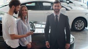 Erfolgreiches Abkommen zwischen Autoverk?ufer und jungen Paaren im Auto-Vertragsh?ndler stock footage