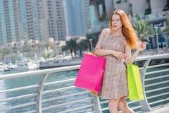 Erfolgreiches Einkaufen Junges Mädchen, das Einkaufstaschen während retu hält Lizenzfreies Stockfoto