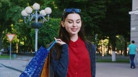 Erfolgreiches Einkaufen Stilvolle Frau, die hinunter die Straße mit Einkaufstaschen geht stock footage