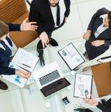 Erfolgreiches Geschäftsteam, das Grafiken bei einem Arbeitstreffen vermarktend sich bespricht Lizenzfreie Stockbilder