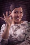 Erfolgreiches glückliches Mädchen, das OKAYgeste zeigt Stockfotografie