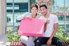 Erfolgreiches kooperatives Einkaufen Paare, die auf einer Bank sitzen und Stockfotos