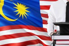 Erfolgreiches malaysisches Studentenausbildungskonzept Halten von Büchern und von Staffelungskappe über Malaysia-Flaggenhintergru lizenzfreie abbildung