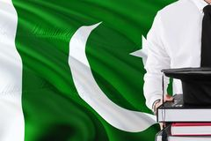 Erfolgreiches pakistanisches Studentenausbildungskonzept Halten von Büchern und von Staffelungskappe über Pakistan-Flaggenhinterg lizenzfreies stockbild