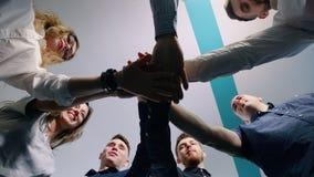 Erfolgreiches Team im Büro: viele Hände, die Stellung im Kreis zusammenhalten Aufschrift der roten Farbe gelegen über Text der we stock video footage