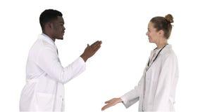 Erfolgreiches Team von den Chirurgen, die hoch fünf geben und von Lachen lokalisiert auf weißem Hintergrund auf weißem Hintergrun stockbilder