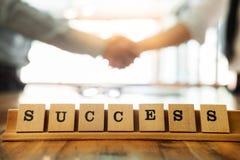 Erfolgswort auf hölzerner Tabelle mit rüttelndem durin Hände des Geschäftsmannes Stockfotos