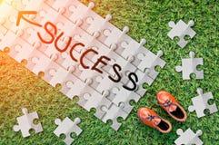 Erfolgswort auf Papierpuzzlespiel mit Lederschuh auf Grasboden Lizenzfreie Stockbilder