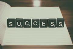 Erfolgswort von den schwarzen Plastikblöcken auf Notizbuch mit Weinlesefilter Lizenzfreies Stockfoto