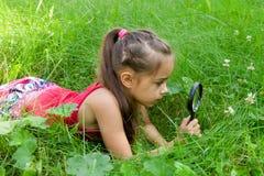 Erforschungsnatur des jungen Mädchens, die Lupe betrachtet Stockfotografie
