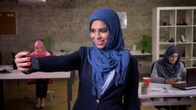 Erfreuliche arabische Frau ist lächelnd stehend und nehmend selfie im blauen hijab und gerade konzentriert auf die frocess, Innen stock video