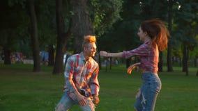 Erfreulicher Junge züchtet seine Freundin in seinen Armen im Park und untersucht liebevoll ihre Augen, glückliche Zeit zusammen stock video footage