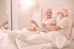 Erfreute ältere Frau, die nahe ihrem Ehemann sitzt stockbilder