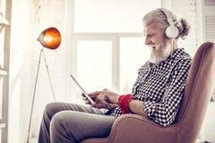Erfreute ältere männliche Person, die entlang seines Geräts anstarrt lizenzfreies stockbild