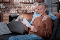 Erfreute ältere Menschen, die ihre Pension überprüfen stockfotografie