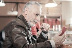 Erfreute bärtige männliche Person, die on-line-Kommunikation hat stockbilder