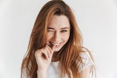 Erfreute Frau in der zufälligen Kleidung blinzelt ihr Auge Stockbild