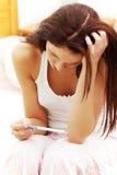 Erfreute Frau, die eine Schwangerschaftprüfung anhält. lizenzfreies stockfoto