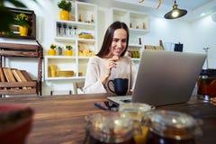 Erfreute Frau, die einen Keks bei der Anwendung eines Laptops hält Stockbild