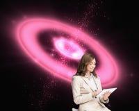 Erfreute Geschäftsfrau, die einen Tabletten-PC sitzt auf Stuhl verwendet Stockfotos