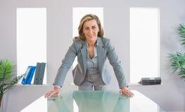 Erfreute Geschäftsfrau, die vor einem Schreibtisch steht Stockfoto