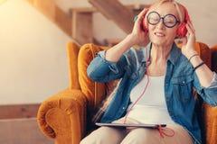 Erfreute Greisin, welche die Musik genießt stockfotos