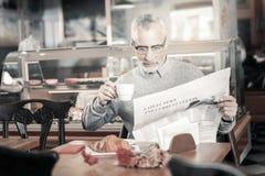 Erfreute reife männliche Person, die Morgenkaffee genießt stockfoto