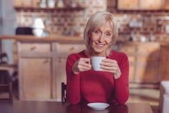 Erfreute weibliche Person, die Kaffeepause hat lizenzfreie stockfotografie