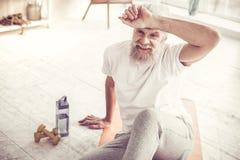 Erfreuter bärtiger Mann, der auf Eignungsmann sitzt lizenzfreie stockfotos