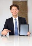 Erfreuter Geschäftsmann, der auf eine leere Tablette zeigt stockbilder